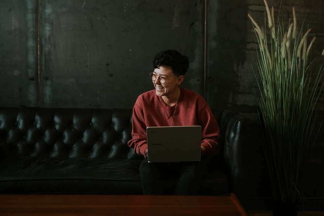 A LGBTQPLUS woman laughs as she listens to a passion fruut youtube video. She is sitting on a black leather sofa using her computer. She has a red jumper, short hair and glasses.
