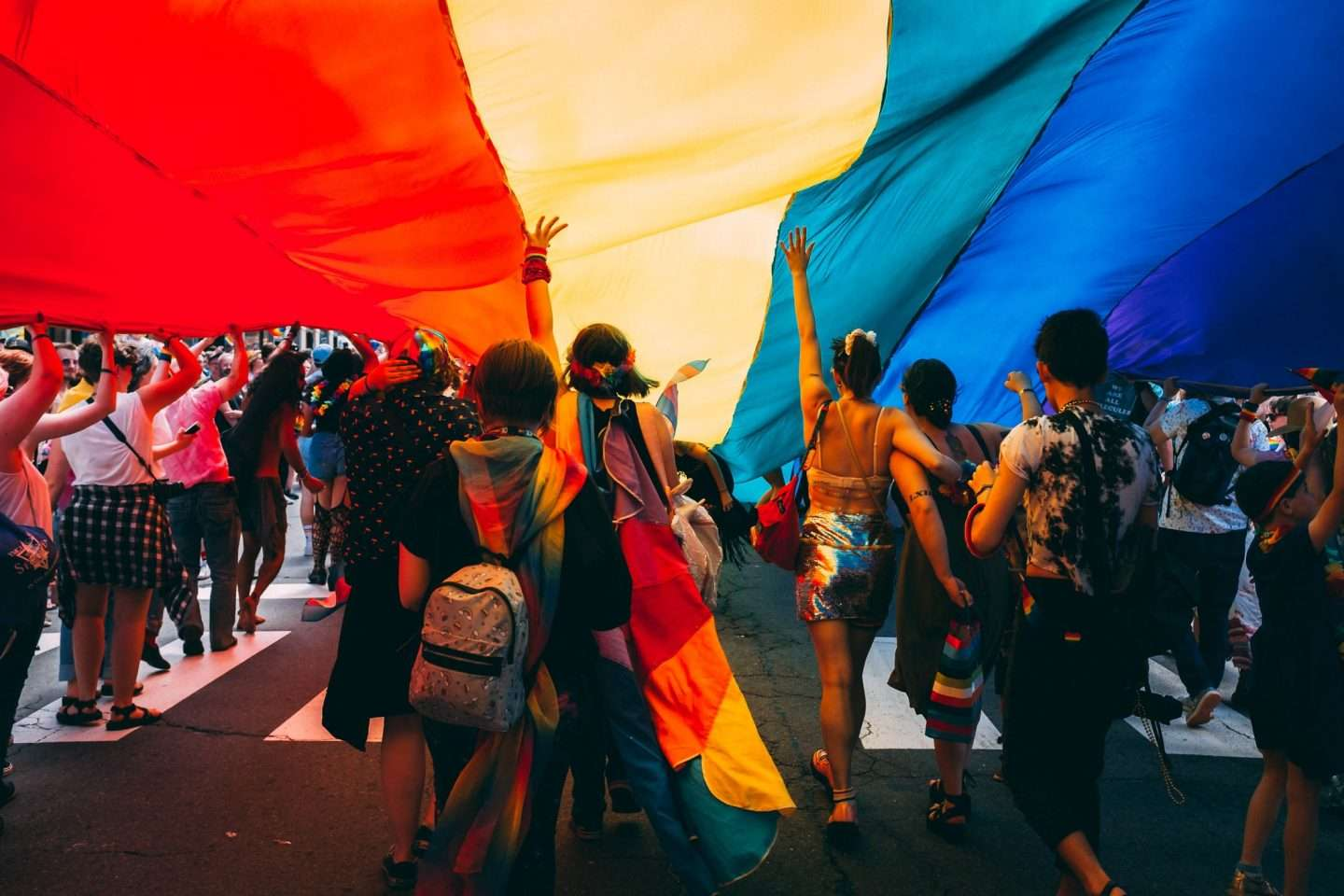 People walking under a Pride flag